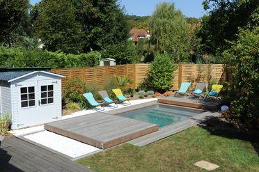 La terrasse coulissante une fois ouverte constitue la plage bois au bord de la piscine.
